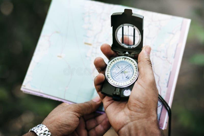 Mani che tengono mappa e bussola immagine stock