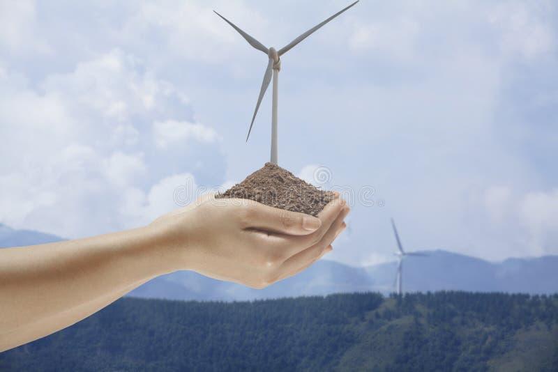 Mani che tengono suolo con un generatore eolico che cresce fuori dal mezzo fotografie stock