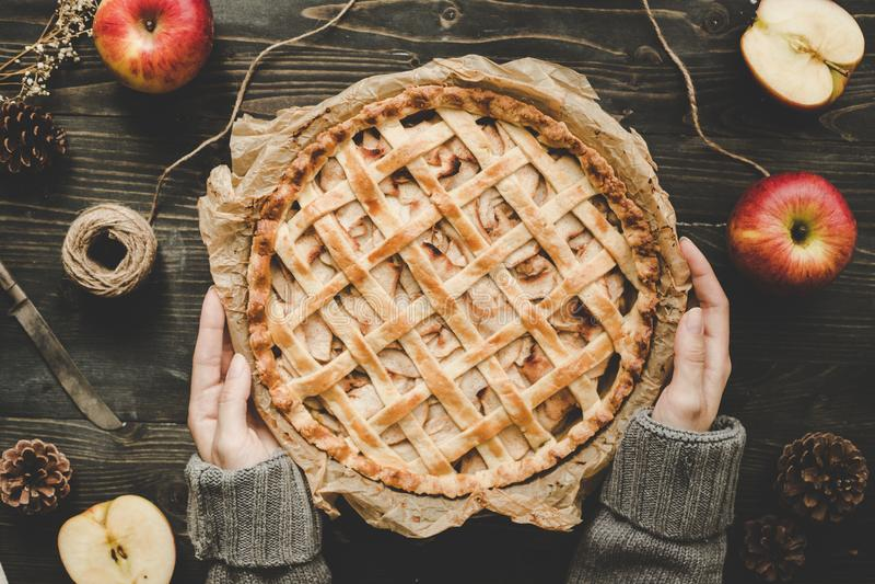 Mani che tengono torta di mele deliziosa casalinga sulla tavola di legno Vista superiore fotografia stock