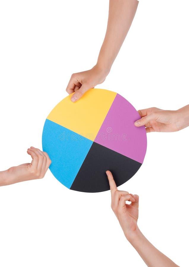 Mani che tengono un cerchio cromatico immagine stock