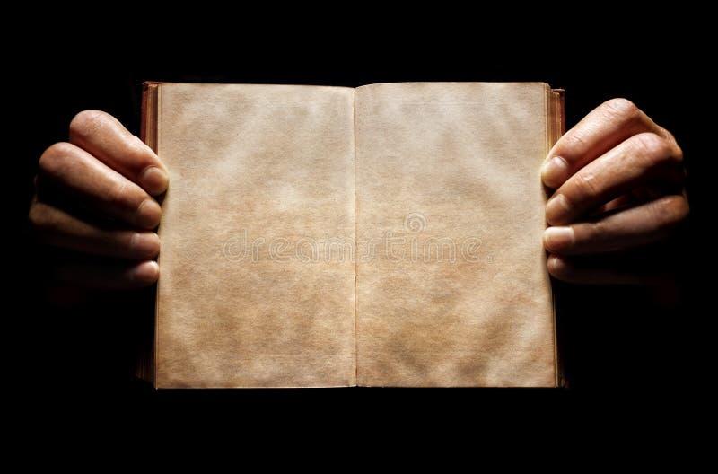 Mani che tengono un fondo vuoto aperto del libro fotografia stock