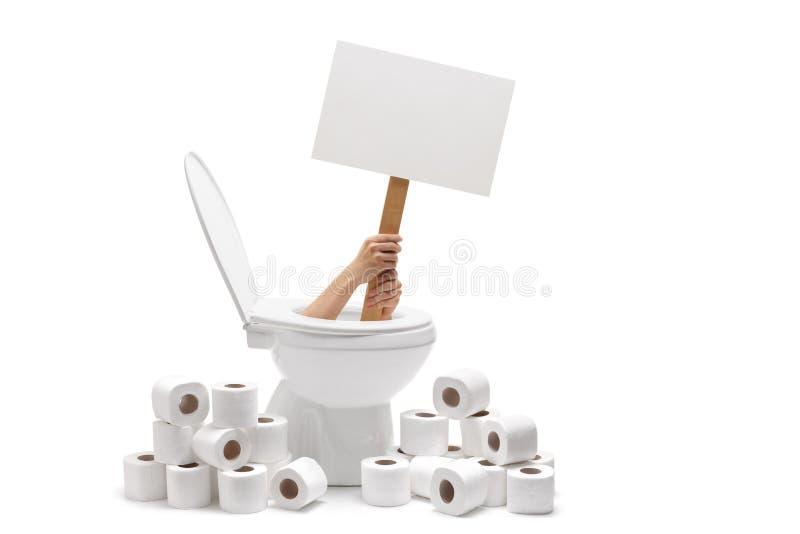 Mani che tengono un'insegna in bianco da una toilette fotografie stock