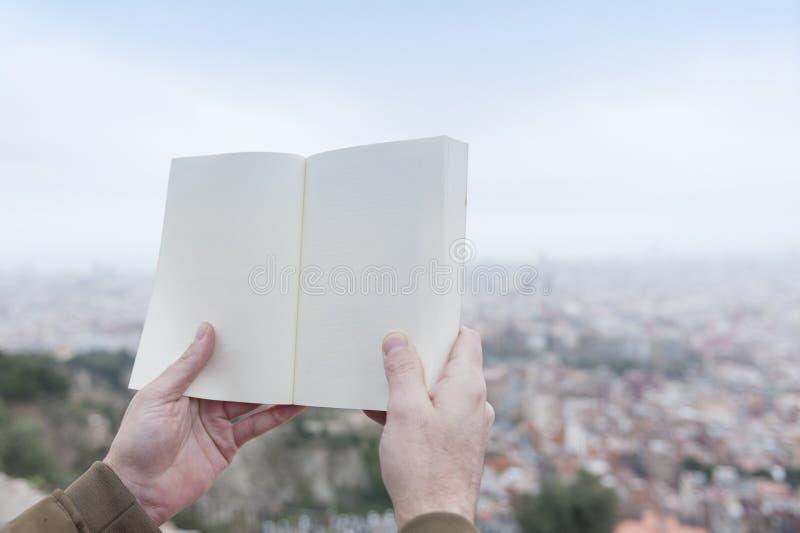 Mani che tengono un libro in bianco immagini stock libere da diritti