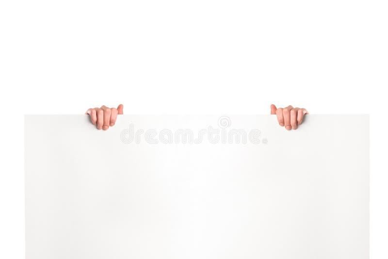 Mani che tengono un tabellone per le affissioni in bianco fotografie stock