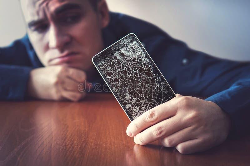Mani che tengono un telefono cellulare con uno schermo rotto sopra il woode immagini stock