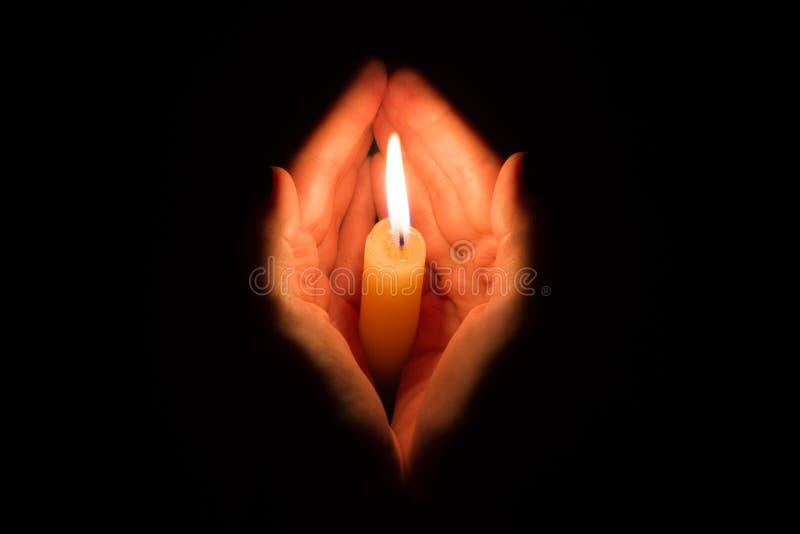 Mani che tengono una candela bruciante immagine stock
