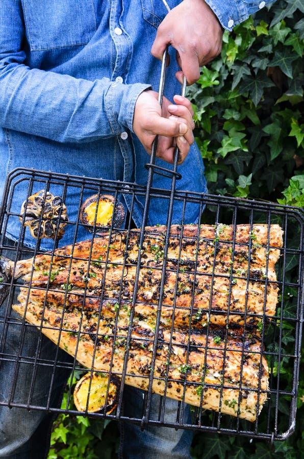 Mani che tengono una griglia che contiene un pesce barbequed immagine stock