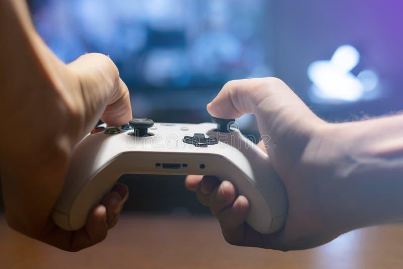 Mani che tengono una leva di comando e giocare i video giochi a casa nella notte f fotografia stock libera da diritti