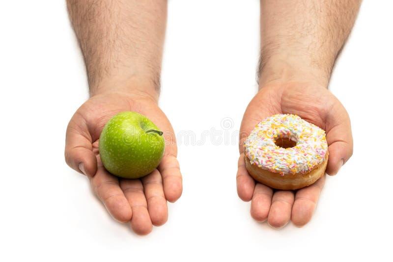 Mani che tengono una mela e un concetto della ciambella di una decisione difficile fra l'alimento sano di alternative opposte con fotografia stock libera da diritti