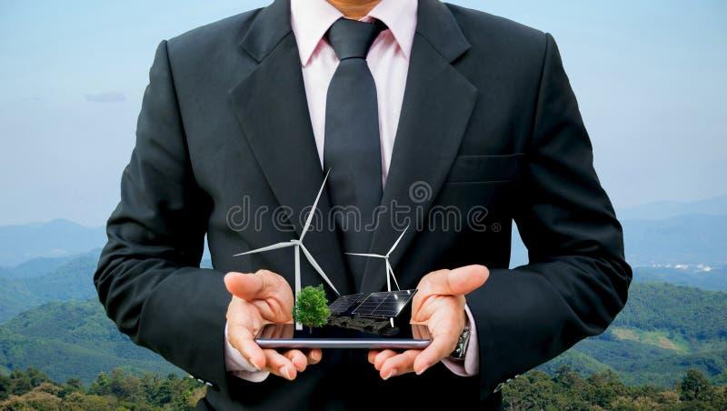 Mani che tengono uomo d'affari su un generatore eolico pulito di energia elettrica dell'albero dello smartphone e su una pila sol immagini stock