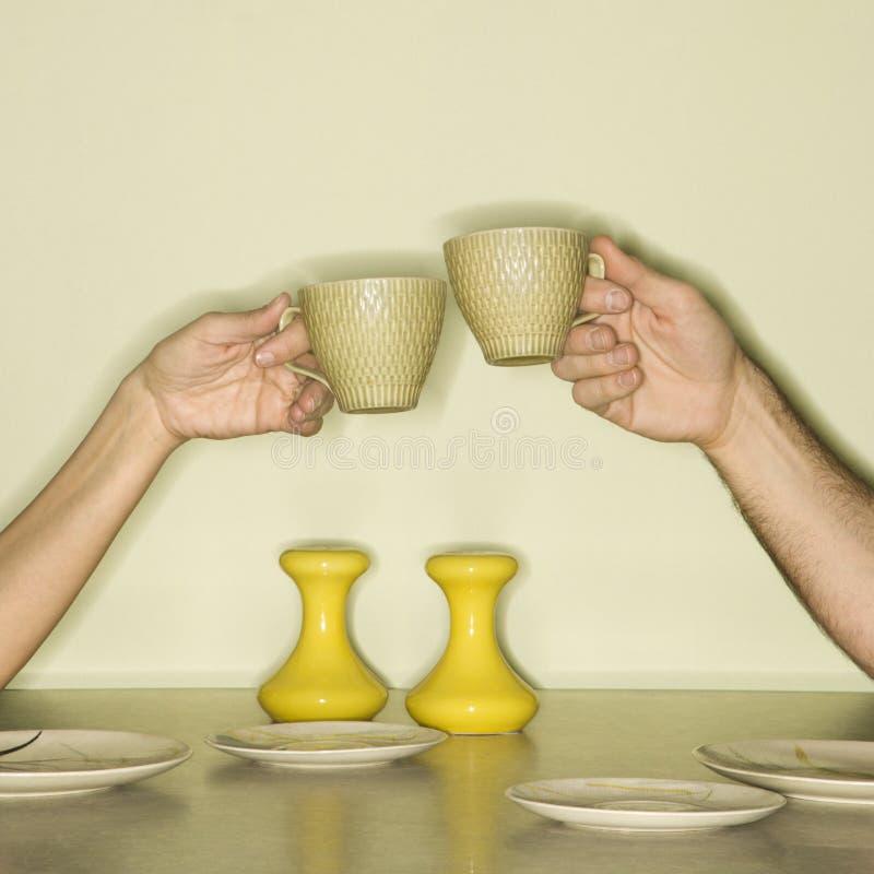Mani che tostano le tazze. fotografia stock