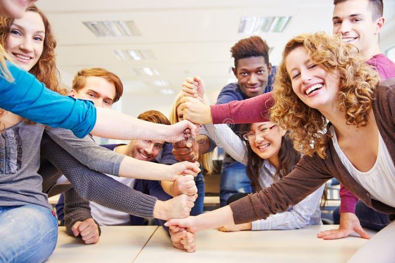 Mani come simbolo per lavoro di squadra nella classe fotografia stock libera da diritti