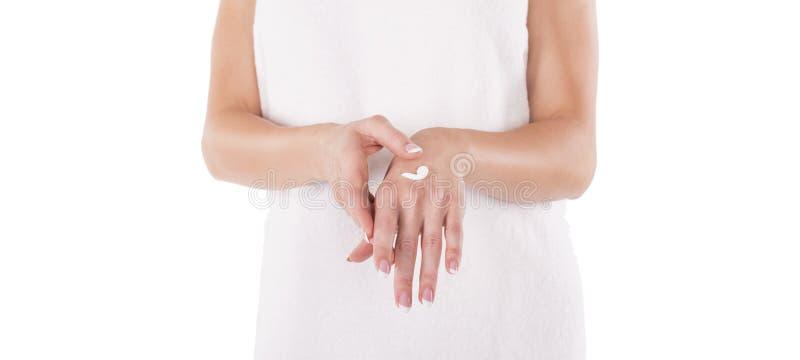 Mani con crema isolata su bianco La donna applica la crema immagini stock