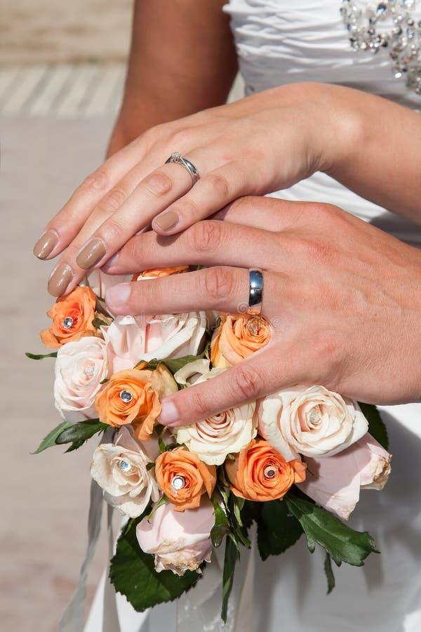 Mani con gli anelli ed il mazzo del fiore immagini stock