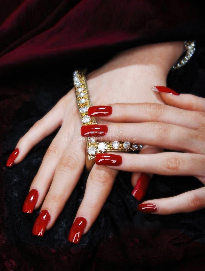 Mani con i chiodi rossi lunghi fotografia stock