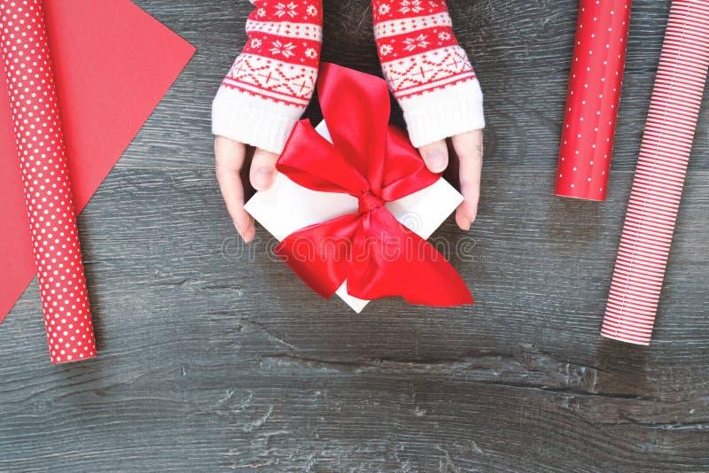 Mani con il contenitore di regalo di Natale e la carta da imballaggio rossa fotografie stock libere da diritti