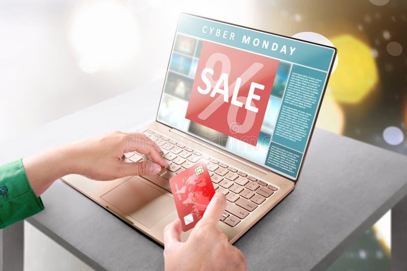 Mani con la carta di credito della tenuta del computer portatile per il pagamento online di acquisto immagine stock