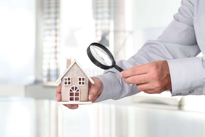 Mani con la casa e la lente d'ingrandimento, casa di ricerca immagini stock libere da diritti