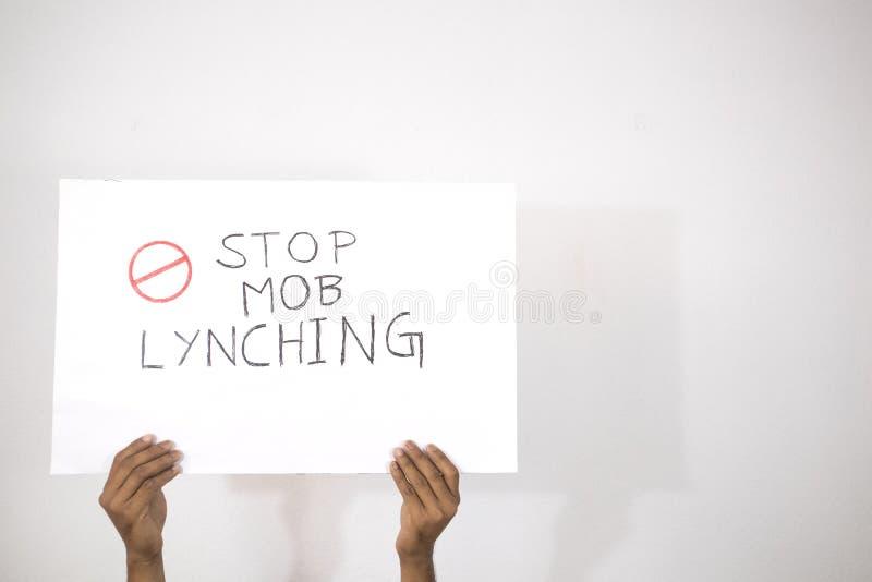 Mani con la mostra Placard di Stop Mob Lynching su sfondo isolato fotografie stock