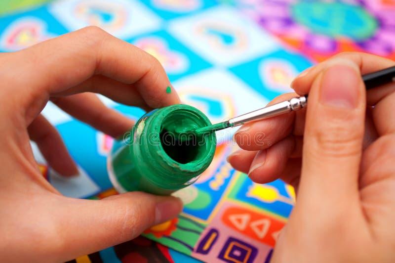 Mani con la spazzola e la vernice fotografia stock