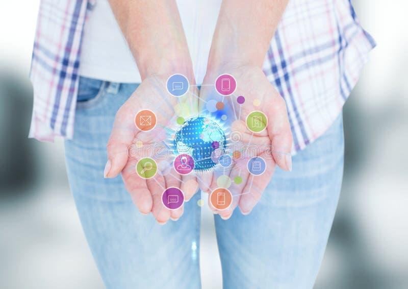 mani con le icone dell'applicazione e mondo con i chiarori fotografie stock libere da diritti