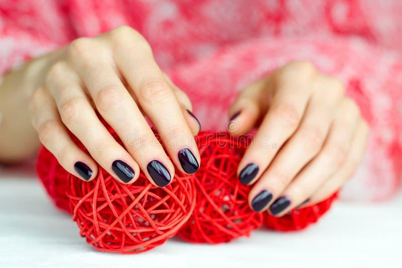 Mani con le palle commoventi della decorazione del manicure immagini stock libere da diritti