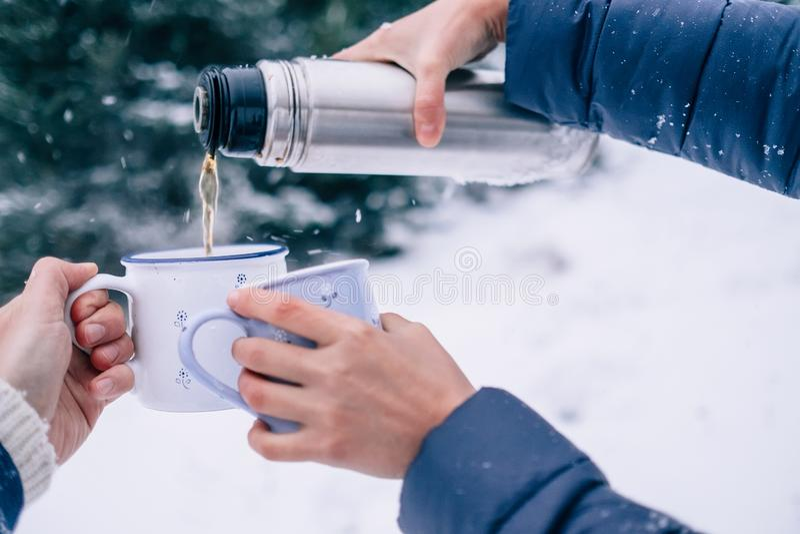 Mani con le tazze della boccetta del termos e del tè nella foresta nevosa di inverno fotografia stock