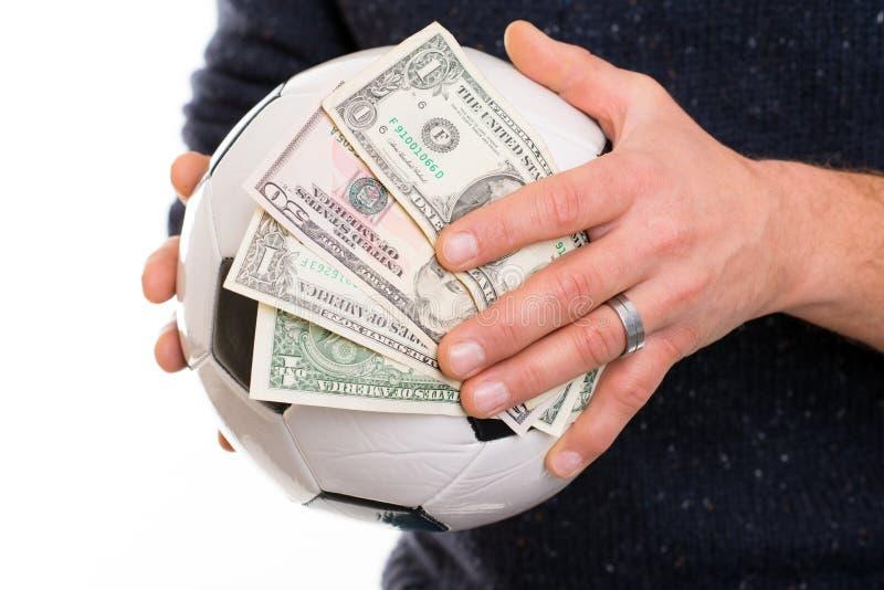 Mani con pallone da calcio e soldi fotografia stock