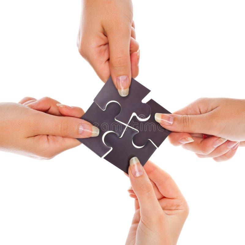 Mani con quattro puzzle immagine stock libera da diritti