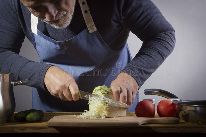 Mani con un coltello per tagliare il cavolo fotografia stock libera da diritti
