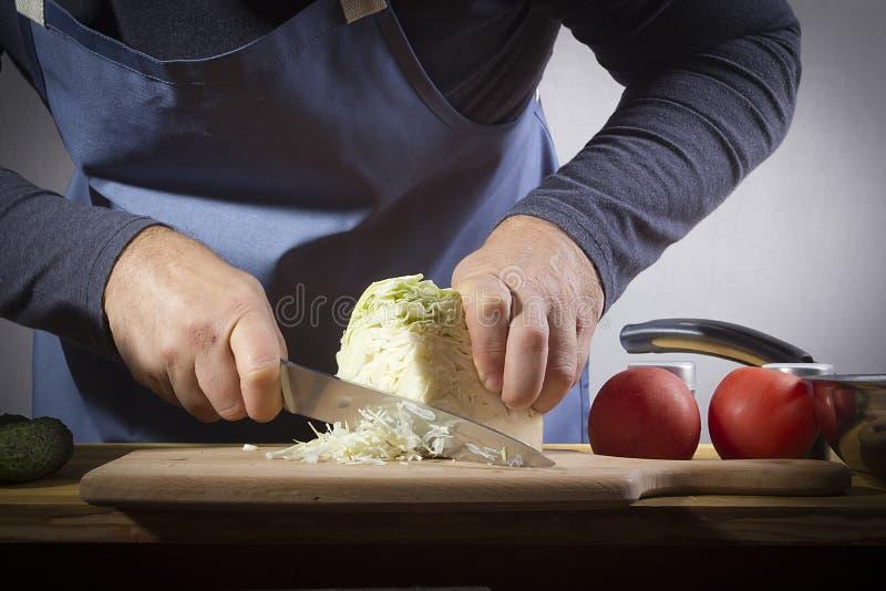 Mani con un coltello per tagliare il cavolo fotografia stock