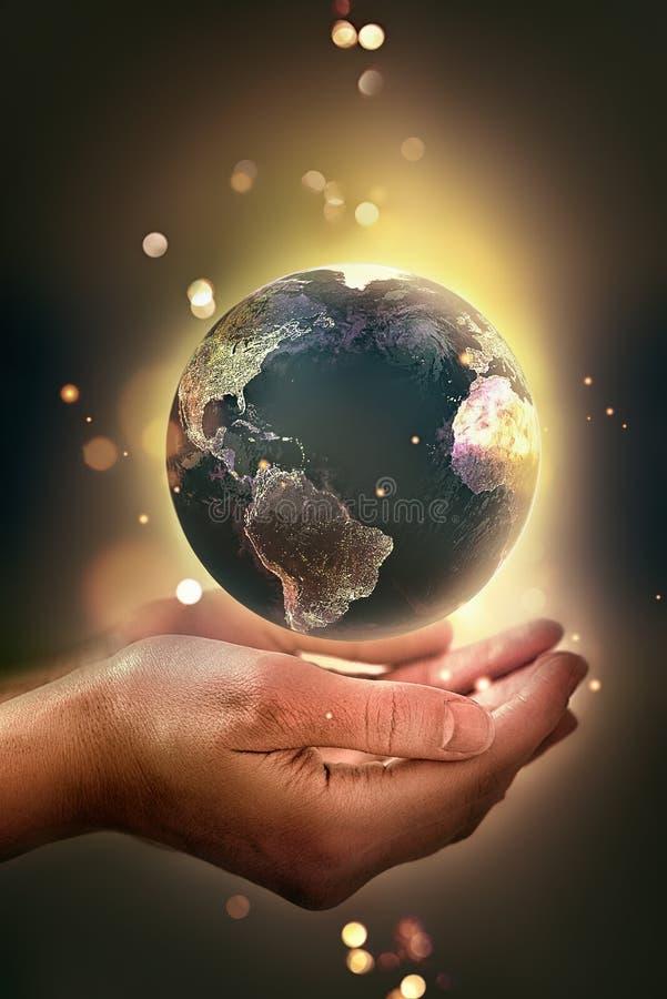 mani con un pianeta d'ardore fotografia stock libera da diritti
