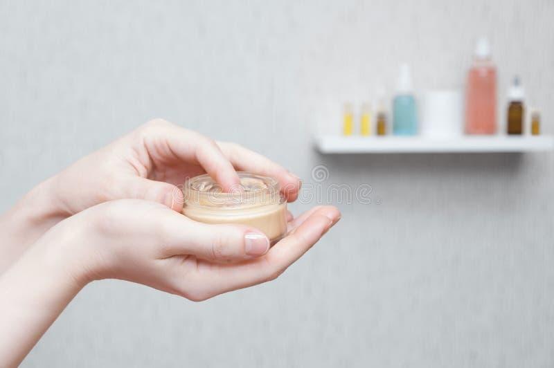 Mani con una latta del primo piano crema fotografie stock