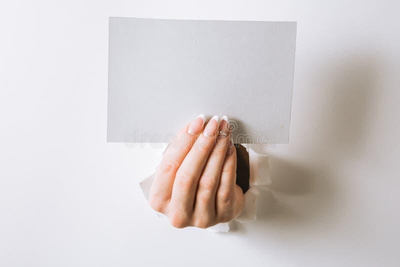 Mani con una perforazione di biglietto da visita un foro in un fondo bianco fotografia stock libera da diritti