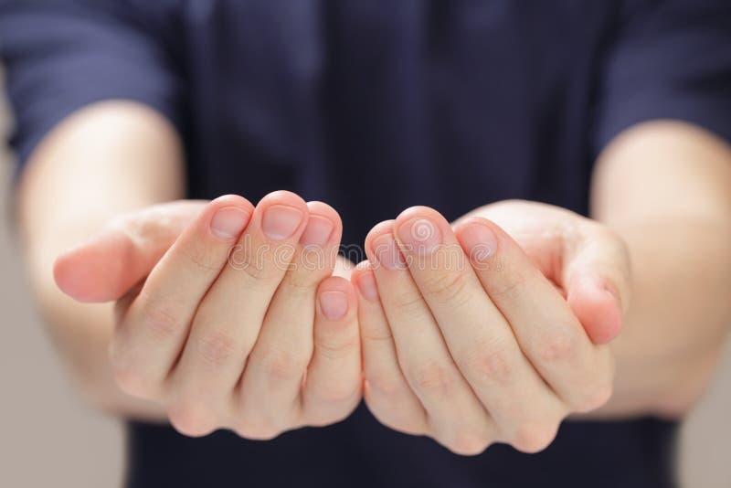 Mani a coppa dell'uomo adulto che mostrano qualcosa immagini stock