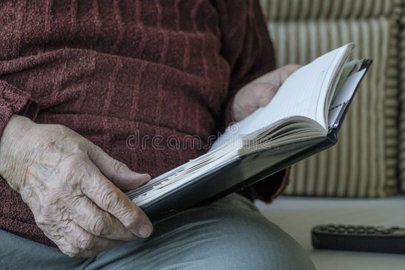 Mani corrugate di una persona che tiene un libro immagine stock libera da diritti