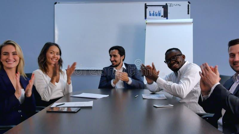 Mani d'applauso soddisfatte del gruppo fiero di affari ed esaminare macchina fotografica in un ufficio moderno fotografia stock