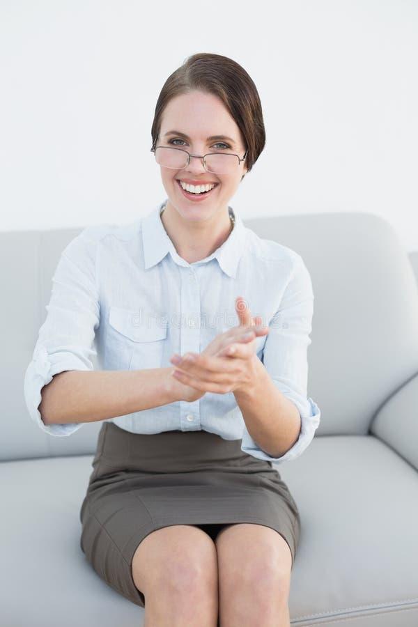 Mani d'applauso sorridenti della donna astuta sul sofà fotografia stock