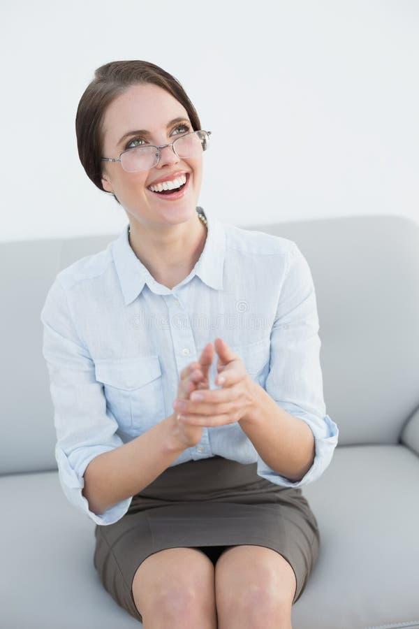 Mani d'applauso sorridenti della donna ben vestito sul sofà immagini stock libere da diritti