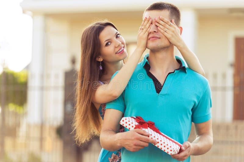 Mani degli occhi dell'uomo della copertura della donna immagini stock