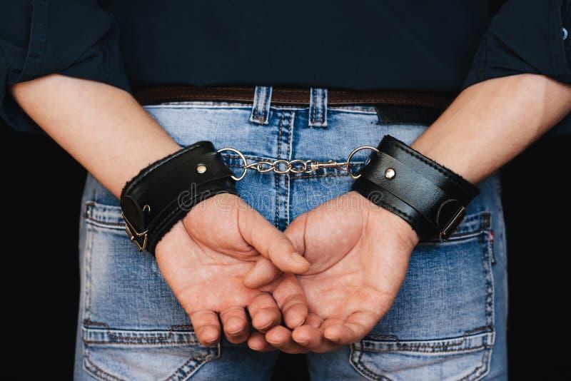 Mani degli uomini in polsini di cuoio dietro la mia parte posteriore immagine stock