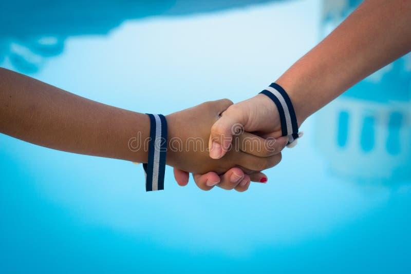 Mani dei bambini che stringono sopra il fondo dell'acqua blu fotografia stock