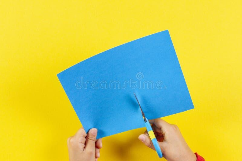 Mani dei bambini che tagliano carta colorata con forbici fotografie stock libere da diritti