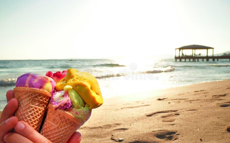 Mani dei bambini che tengono il gelato sulla spiaggia immagini stock libere da diritti