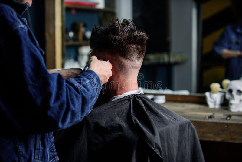Mani dei capelli della guarnizione del barbiere del tipo barbuto con il tagliatore ed il pettine, fine sulla retrovisione Concett immagine stock libera da diritti