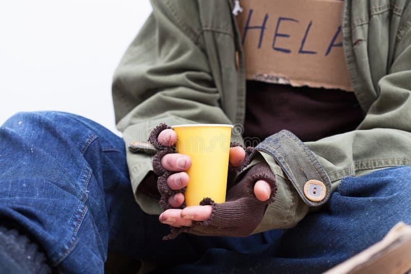 Mani dei senzatetto con una tazza di carta fotografie stock