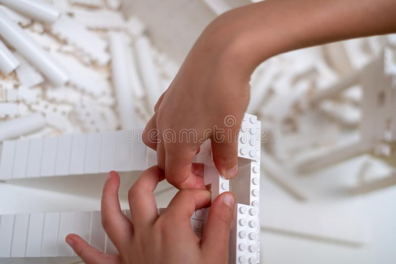 Mani del bambino che giocano con i mattoni bianchi di Lego nella turbina Corridoio a Tate Modern, Londra Regno Unito fotografia stock