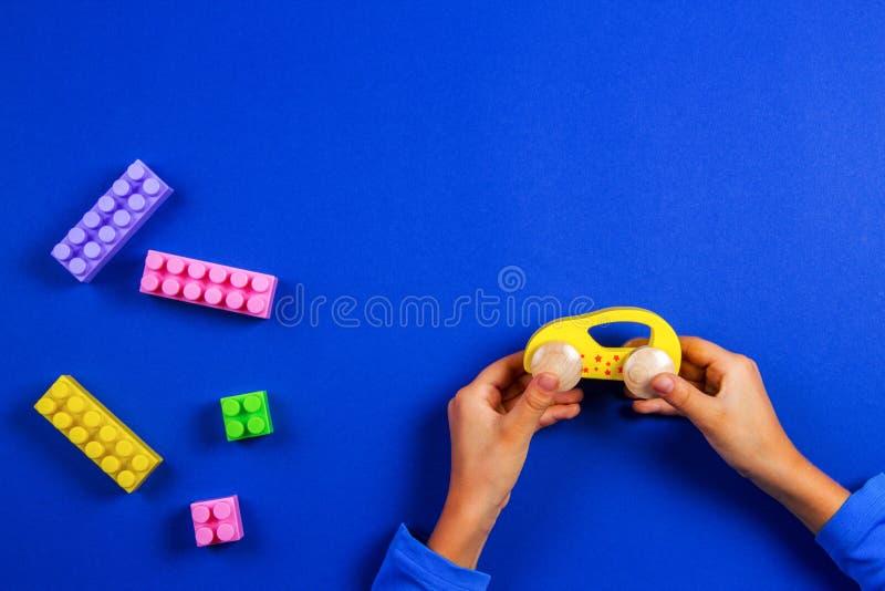 Mani del bambino che giocano con l'automobile di legno del giocattolo su fondo blu fotografia stock