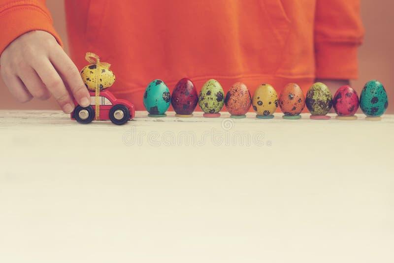 Mani del bambino che giocano l'uovo di Pasqua sull'automobile sulla tavola di legno Concetto di festa immagini stock libere da diritti