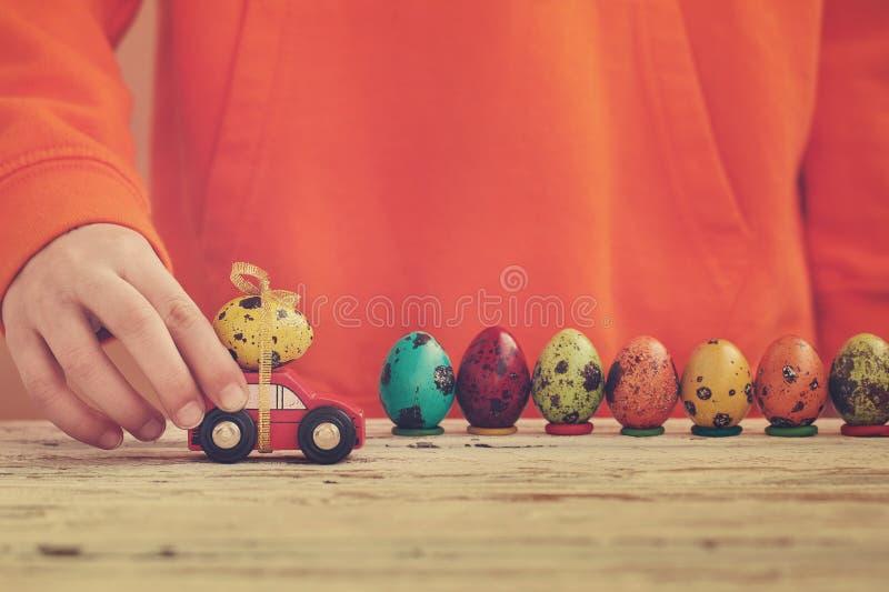 Mani del bambino che giocano l'uovo di Pasqua sull'automobile sulla tavola di legno Concetto di festa fotografia stock